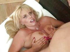 Chubby blonde with black corset doing titjob with her massive jugs
