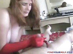 Busty mature plumper brunette strokes his cock with her red gloved hands