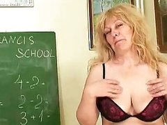 Aged blonde teacher with huge tits inserting an toy in the classroom