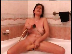 Turbulent piece of stray with an idyllic giner diddles herself in the tub with a huge dildo